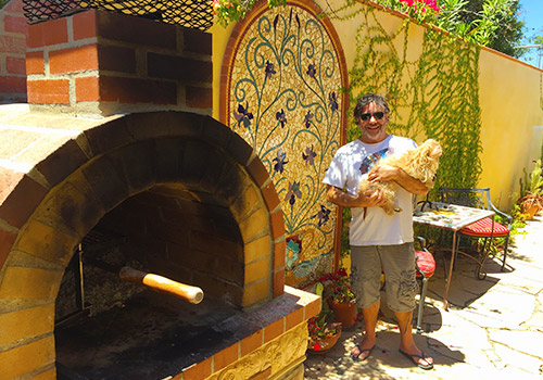 Carmelo Fiannaca's outdoor oven, which is next to one of his mosaic art pieces, shows his love of cooking