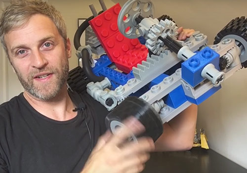 YouTube host Matt Denton holds up a 3D-printed LEGO creation on his 'Mantis Hacks'